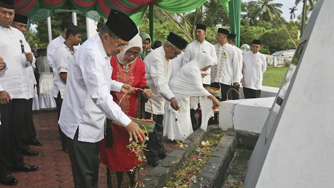 Indonesian Vice President Jusuf Kalla sprinkles flowers during a ceremony commemorating the 10th anniversary of the Indian Ocean tsunami at a mass grave in Aceh Besar, Aceh province, Indonesia, Friday, Dec. 26, 2014. The devastating Dec. 26, 2004 tsunami struck a dozen countries around the Indian Ocean rim, killing 230,000 people, most of them in Aceh. (AP Photo/Binsar Bakkara)