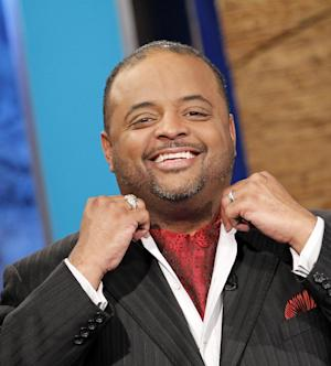 """FILE -- In a May 14, 2010 photo Roland Martin, wearing an ascot, adjusts his collar before a news segment in Washington.  CNN suspended political analyst Martin on Wednesday Feb. 8, 2012 for """"offensive"""" tweets during the Super Bowl (AP Photo/Haraz N. Ghanbari, file)"""