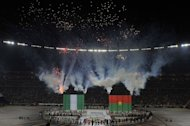 Artists perform around giant Nigerian and Burkina Faso flags during a ceremony held ahead of the kick off of the 2013 African Cup of Nations final football match between Burkina Faso and Nigeria on February 10, 2013 at Soccer City stadium in Johannesburg