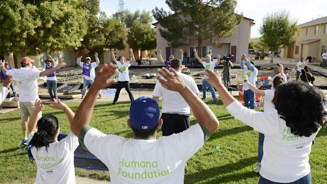 IMAGE DISTRIBUTED FOR HUMANA -Volunteers warm-up together before joining forces to build a one-of-kind, multi-generational playground at the Las Casas Housing Development in Coachella, Calif, on Saturday, December 1, 2012. More than 200 volunteers joined The Humana Foundation, the philanthropic arm of Humana, Inc., one of the nation's leading health care companies; KaBOOM!, a national non-profit dedicated to saving play; the Family YMCA of the Desert, the largest provider of licensed childcare in the Coachella Valley; and the Coachella Valley Housing Coalition, an award-winning non-profit housing development corporation, to build the playground in just six hours. The playground build is one of many wellness-focused activities taking place leading up to the 2013 Humana Challenge golf tournament to be held Jan. 14-20, 2013, in La Quinta, Calif. The build is a direct result of the collective efforts of thousands of people who wore Humana pedometers and logged their steps during the 2012 Humana Challenge Walkit program. Every step counted toward the donation made by the Humana Foundation. (Rodrigo Pena / AP Images for Humana)