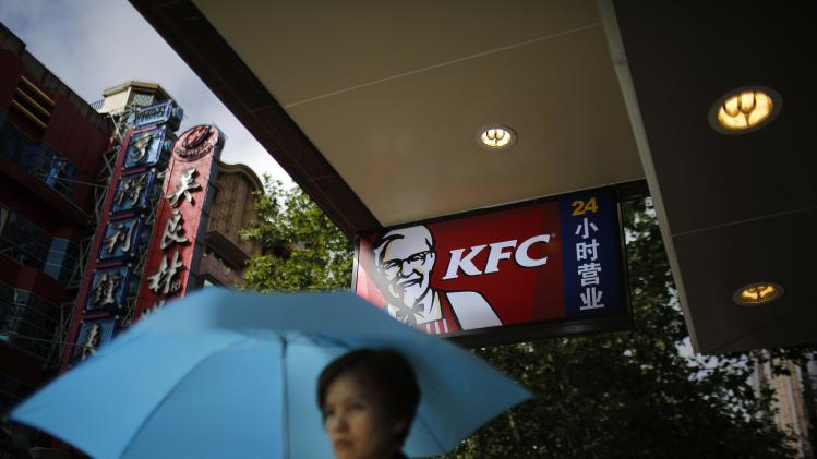 A woman walks by a KFC store in downtown Shanghai