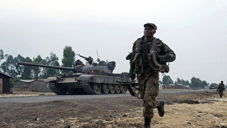 A Congolese soldier runs past a tank in Kanyarucinya, around 10 km from Goma in DR Congo on July 17, 2013