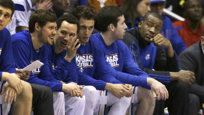 Kansas forward Cliff Alexander, right, sits at the end of the bench during the first half of an NCAA college basketball game against Texas at Allen Fieldhouse in Lawrence, Kan., Saturday, Feb. 28, 2015. Alexander was held out of Saturday's game after questions were raised about the five-star freshman's eligibility. (AP Photo/Orlin Wagner)