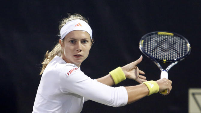 Stefanie Voegele, of Switzerland, returns to Julia Goerges, of Germany, at the Family Circle Cup tennis tournament in Charleston, S.C., Thursday, April 4, 2013. (AP Photo/Mic Smith)
