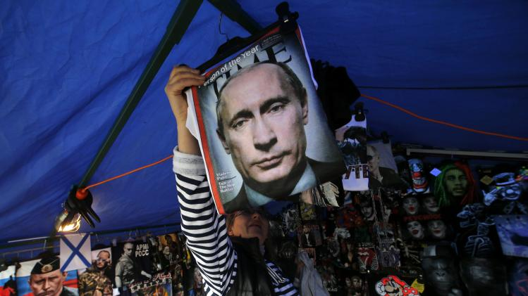 A vendor sells T-shirts printed with images of Russia's President Vladimir Putin at a street store in the center of St. Petersburg