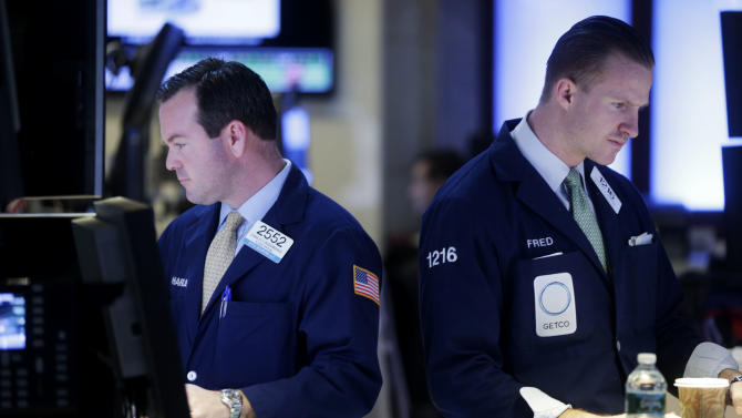 """Traders work on the floor at the New York Stock Exchange in New York, Wednesday, Jan. 2, 2013. The """"fiscal cliff"""" compromise, for all its chaos and controversy, was enough to send the stock market shooting higher Wednesday, the first trading day of the new year. (AP Photo/Seth Wenig)"""