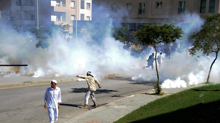 "Demonstrators throw stones during a protest against the anti-Islam film ""Innocence of Muslims"" outside the U.S. Embassy in Tunis, Tunisia, as police respond with tear gas Friday, Sept. 14, 2012. Protests against he film spread to their widest extent yet around the Middle East and other Muslim countries Friday, as protesters smashed into the German Embassy in the Sudanese capital and security forces in Egypt and Yemen fired tear gas and clashed with protesters to keep them away from U.S. embassies. (AP Photo/Hassene Dridi)"