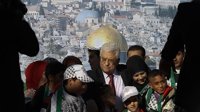 Palestinian President Mahmoud Abbas, center, is surrounded by children during celebrations for the successful bid to win U.N. statehood recognition for Palestine in the West Bank city of Ramallah, Sunday, Dec. 2, 2012. Abbas has returned home to a hero's welcome after winning a resounding endorsement for Palestinian independence at the United Nations. Israel on Sunday roundly rejected the United Nations' endorsement of an independent state of Palestine, announcing it would withhold more than $100 million collected for the Palestinian government to pay debts to Israeli companies and earlier said it would start drawing up plans to build thousands of settlement homes. (AP Photo/Nasser Shiyoukhi)
