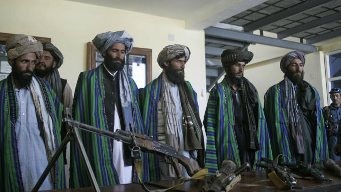 Former Taliban fighters hand over their weapons to Afghan police as part of a reconciliation process in Herat, Afghanistan, Sunday, May 13, 2012.  As the U.S. and NATO prepare for the downsizing of international troops with a final withdrawal scheduled for 2014 efforts are underway to bring the Taliban off the battlefield. Taliban leaders including one of the most senior members of the organization, Agha Jan Motasim told The AP that most Taliban supported a negotiated end to the protracted war in Afghanistan. (AP Photo/Hoshang Hashimi)