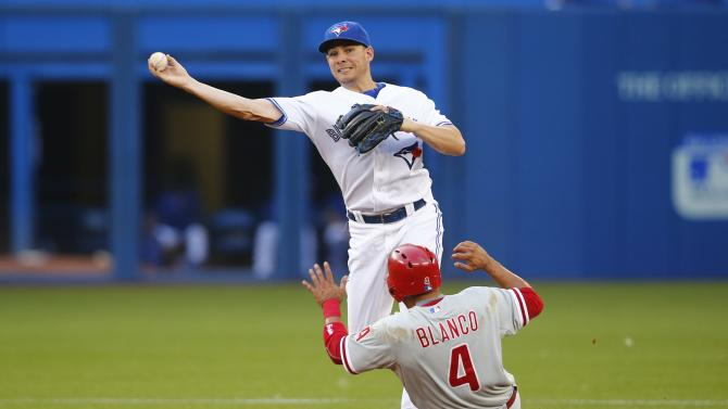 Toronto Blue Jays' Danny Valencia turns a double pay over Philadelphia Phillies' Andres Blanco, right, during the third inning of an interleague baseball game, Tuesday, July 28, 2015 in Toronto. (Mark Blinch/The Canadian Press via AP) MANDATORY CREDIT