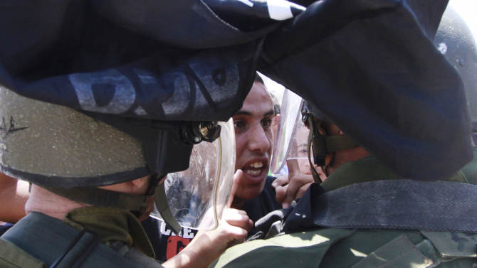 """A Palestinian protester argues with Israeli border policemen during a rally to commemorate the 1948 creation of the Israel state known in Arabic as the """"Nakba Day"""", or """"Day of the Catastrophe"""" outside the West Bank town of  Bethlehem, Tuesday, May 14, 2013. (AP Photo/Nasser Shiyoukhi)"""