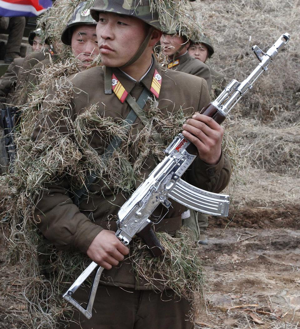 In this Sunday, March 4, 2012 photo, North Korean soldiers, including one carrying a weapon that military personnel say was given to them by North Korean leader Kim Jong Un,  gather at a military base on North Korea's southwest coast, opposite South Korea's Baengnyeong Island. (AP Photo/Kim Kwang Hyon)