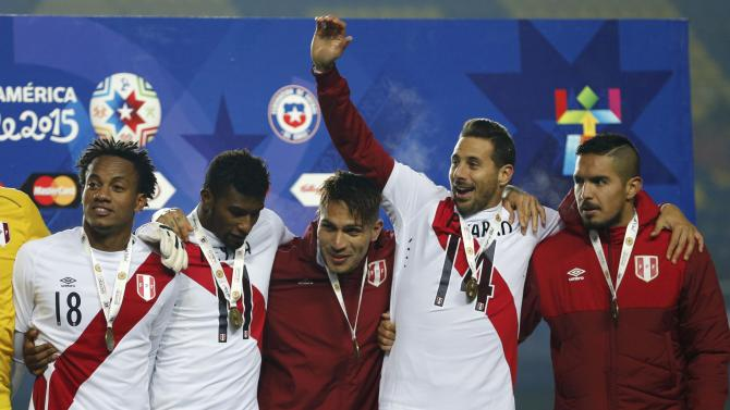 Peru players wear their medals as they acknowledge the fans following their victory over Paraguay in their Copa America 2015 third-place soccer match at Estadio Municipal Alcaldesa Ester Roa Rebolledo in Concepcion