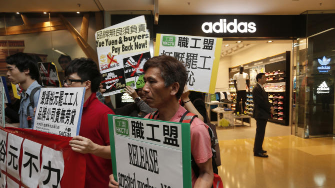FILE - In this April 24, 2014 file photo, protesters from labor organizations hold banners and placards during a protest to support workers on strike at Yue Yuen Industrial Holdings Ltd. outside a Adidas shop at a shopping mall in Hong Kong. Most of the tens of thousands of workers who were striking at a massive Chinese shoe factory complex have returned to the job, labor activists said Saturday, April 26, enabling Adidas to resume production there. The Germany-based athletic wear giant said workers returned Friday to its factory run by Taiwanese-owned Yue Yuen Industrial Holdings Ltd., the world's largest manufacturer of athletic shoes. (AP Photo/Vincent Yu, File)