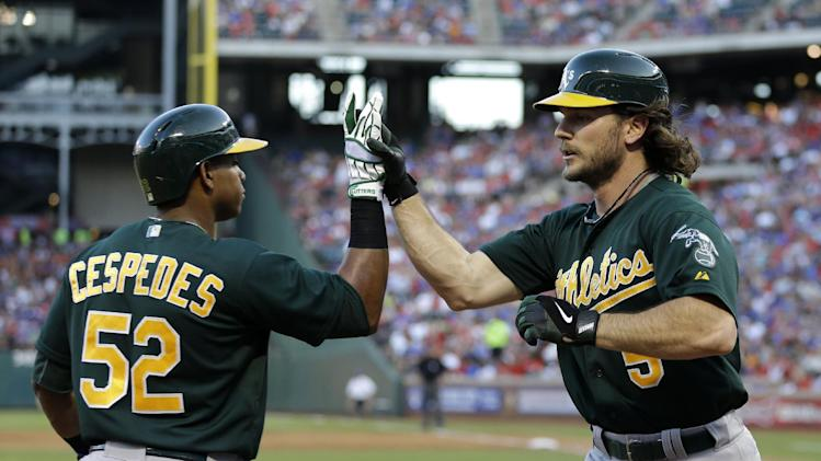 Oakland Athletics' Yoenis Cespedes (52) congratulates John Jaso (5) on his solo home run that came off a pitch from Texas Rangers' Yu Darvish in the second inning of a baseball game Tuesday, June 18, 2013, in Arlington, Texas. (AP Photo/Tony Gutierrez)