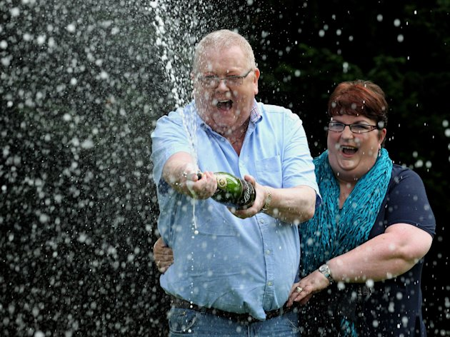 Colin and Chris Weir, from Largs in Ayrshire, celebrate, during a photo call, in Falkirk, Scotland, Friday July 15, 2011, after they scooped 161 million pounds, euro 183 million, $260 million, in Tuesday's EuroMillions draw. Europe's biggest Lottery winners have been unveiled by Camelot. Husband and wife Colin and Chris Weir, from Largs in Ayrshire, scooped 161 million pounds in Tuesday's EuroMillions draw. The couple banked the entire jackpot after several rollovers - a total of 161,653,000 pounds. (AP Photo/Andrew Milligan/PA) UNITED KINGDOM OUT NO SALES NO ARCHIVE