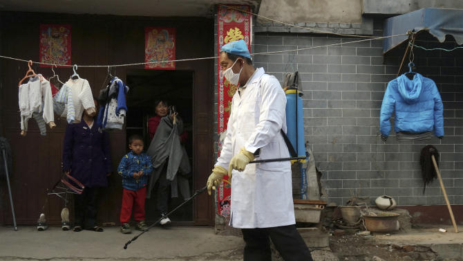 A family watches a worker spray disinfectant in Naidong village, where a boy tested positive for the H7N9 virus, in Beijing Monday, April 15, 2013. The new case of bird flu in China's capital, a 4-year-old boy who displayed no symptoms, is adding to the unknowns about the latest outbreak that has caused 63 confirmed cases and 14 deaths, health officials said Monday. (AP Photo) CHINA OUT