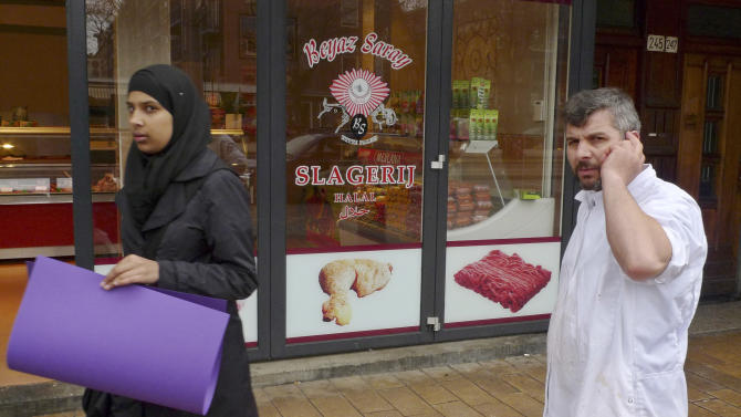 FILE - In this March 31, 2011 file photo a butcher talks on his mobile phone as a veiled woman passes a Halal butchers store in Amsterdam, Netherlands. The Netherlands' parliament is set to pass a bill banning any slaughter of livestock without stunning, removing an exemption that has long allowed orthodox Dutch Jews and Muslims to butcher animals according to their centuries-old dietary rules. The legislation going to a vote Tuesday, June 28, 2011, enjoys support on the political left, which sees ritual slaughter as cruel to animals, and on the right, which sees it as foreign and barbaric. (AP Photo/Peter Dejong, File)