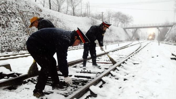 Railway workers clean the snow off a railway track at a station amid heavy snowfall in Xinmi
