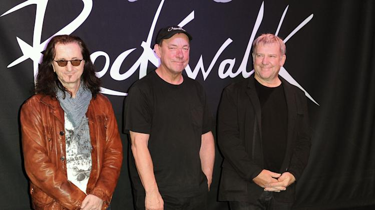 "FILE - This Nov. 20, 2012 file photo shows members of the band Rush, from left, Geddy Lee, Neil Peart, and Alex Lifeson at the RockWalk induction of Rush at Guitar Center in Los Angeles. The eclectic group of rockers Rush and Heart, rappers Public Enemy, songwriter Randy Newman, ""Queen of Disco"" Donna Summer and bluesman Albert King will be inducted into the Rock and Roll Hall of Fame April 18, 2013, in Los Angeles.  (Photo by Richard Shotwell/Invision/AP, file)"