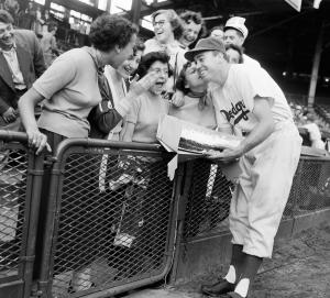 "FILE - In this Sept. 16, 1950, file photo, fans look on as Brooklyn Dodgers center fielder Duke Snider gets a kiss from Kathy Cariani at Ebbets Field in the Brooklyn borough of New York, as the Dodgers met the St. Louis Cardinals in a baseball game. Snider holds a cake foir his 24th birthday Snider, the Hall of Fame center fielder for the charmed ""Boys of Summer"" who helped the Dodgers bring their elusive and only World Series crown to Brooklyn, died Sunday, Feb. 27, 2011. He was 84. Snider died at the Valle Vista Convalescent Hospital in Escondido, Calif., said the National Baseball Hall of Fame and Museum, which announced the death on behalf of the family. (AP Photo/File)"