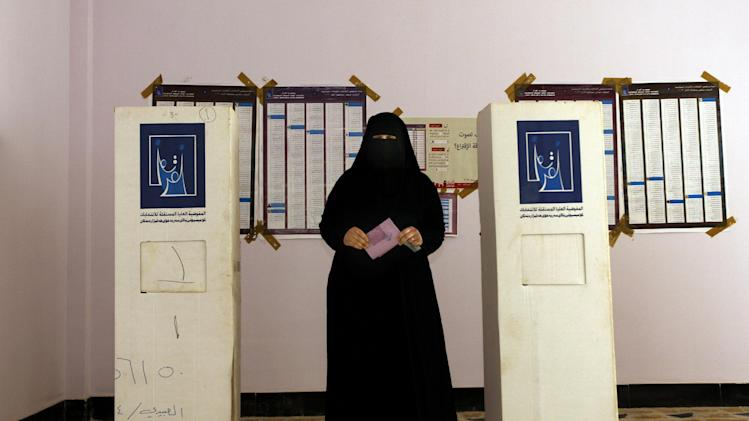 An Iraqi woman prepares to casts her ballot at a polling center during the country's provincial elections in Fallujah, Iraq, Thursday, June 20, 2013. Iraqis in two Sunni-dominated provinces voted Thursday in provincial elections marked by tight security measures that left streets in former insurgent strongholds largely deserted. (AP Photo/ Khalid Mohammed)