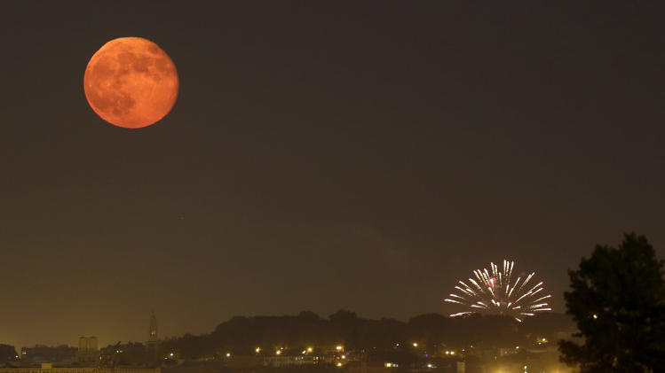 The full moon rises over Brooklyn as amateur fireworks explode are viewed from Bayonne, N.J., Wednesday, July 4, 2012. (AP Photo/Julio Cortez)