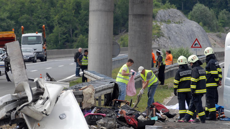 Police and firefighters survey the scene of the bus crash near Gospic, Croatia, Saturday, June 23, 2012. At least seven Czech tourists were killed and 44 injured in a bus crash on a major highway in Croatia early Saturday, police said. The accident happened some 200 kilometers (124 miles) south of Zagreb, on the highway connecting the Croatian capital with the central Adriatic coastal city of Split. (AP Photo) CROATIA OUT