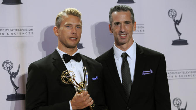 """Dan Savage, right, and Terry Miller pose backstage with the Governors Award for the """"It Gets Better Project"""" at the 2012 Creative Arts Emmys at the Nokia Theatre on Saturday, Sept. 15, 2012, in Los Angeles. (Photo by Chris Pizzello/Invision/AP)"""