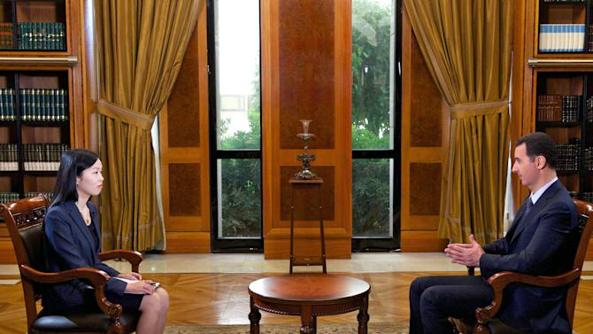 In this photo released by the Syrian official news agency SANA, Syrian President Bashar Assad, right, speaks during an interview with Chinese state CCTV, in Damascus, Syria, Monday, Sept. 23, 2013. Assad said his government will allow international experts access to its chemical weapons sites but cautioned in an interview broadcast Monday that rebels might block them from reaching some of the locations. (AP Photo/SANA)