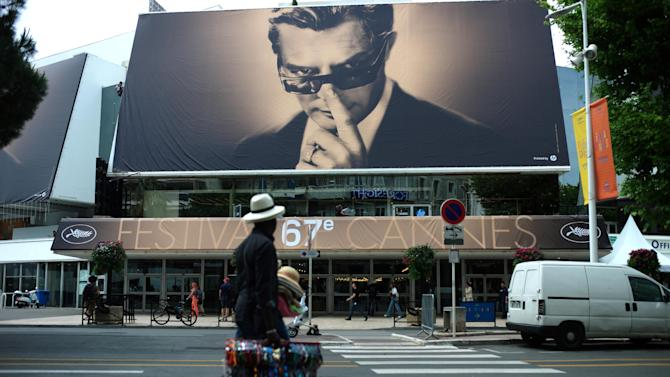 A street vendor walks past a banner depicting Marcello Mastroianni from Federico Fellini's film 8½ on the Palais prior to the 67th international film festival, Cannes, southern France, Monday, May 12, 2014. The festival runs from May 14 to May 25. (AP Photo/Thibault Camus)