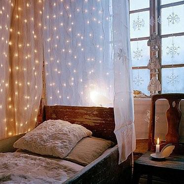 Cascade strings of fairy lights between layers of sheer curtains.   Source