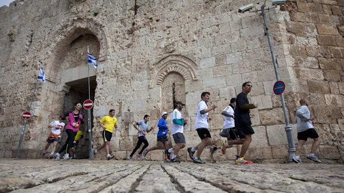 Runners are seen next the Jerusalem's old city Zion Gate during the second annual marathon in Jerusalem, Friday, March 16, 2012.  About 15,000 runners, including 1,500 from overseas, are competing Friday, with some 1,000 competitors expecting to complete the full 42 kilometers (26.2 miles) marathon distance, and others aiming to complete shorter distances, including Mayor Nir Barkat who says he plans to run half a marathon and 77-year old Hanoch Shahar aiming for 10Km.  (AP Photo/Sebastian Scheiner)