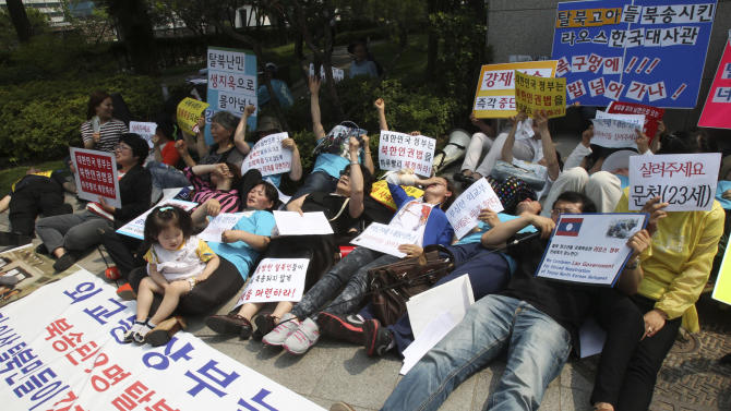"""North Korean defectors stage a die-in during a rally protesting against Laos' repatriation of nine North Korean defectors, in front of Foreign Ministry in Seoul, South Korea, Wednesday, June 5, 2013. The nine defectors, seven male and two female, were flown home from China last week. They had been captured in Laos some 17 days earlier, along with a South Korean missionary who tried to help them take asylum at a foreign embassy in the Southeast Asian country, according to South Korean officials and activists. Before they were captured in Laos and sent home, the young group of North Korean defectors smiled and teased each other as they told an activist how some of them were beaten with sticks for trying to steal noodles in their homeland. Banners read: """"Banning compulsory repatriation is an international law."""" (AP Photo/Ahn Young-joon)"""