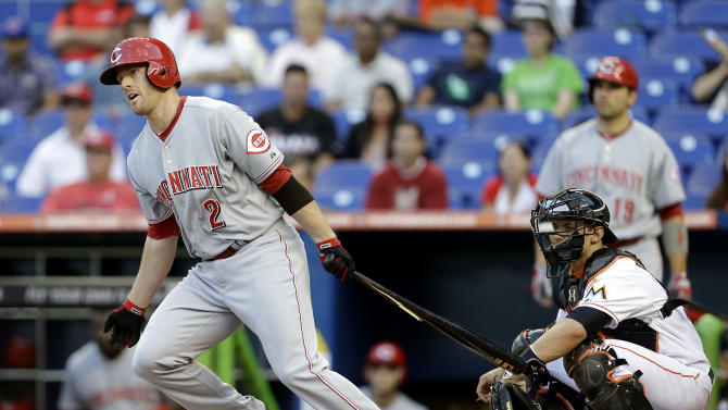 Cincinnati Reds' Zack Cozart (2) watches his double in front of Miami Marlins catcher Rob Brantly, right, during the first inning of a baseball game in Miami, Tuesday, May 14, 2013. (AP Photo/Lynne Sladky)