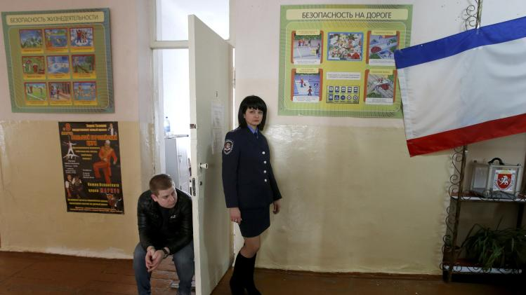 A policewoman and an election official are seen at a polling station in the Crimean town of Simferopol