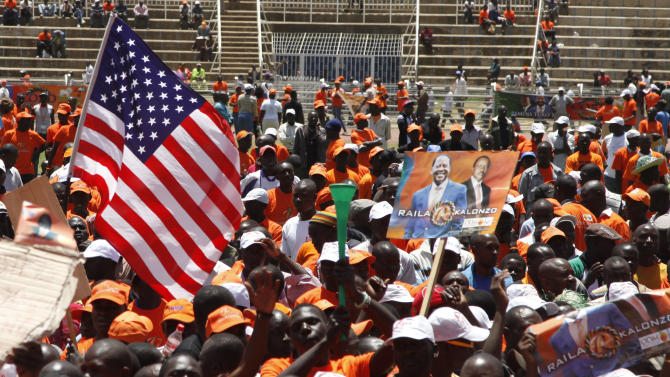 Supporters of Kenyan Prime Minister and Presidential candidate, Raila Odinga, wave an American flag at the Nyayo National Stadium, Nairobi, Kenya, Saturday, March 2, 2013 wait for a rally on the final day of the campaign for the election. Kenya will hold its national election March 4, 2013.(AP Photo/Sayyid Azim)