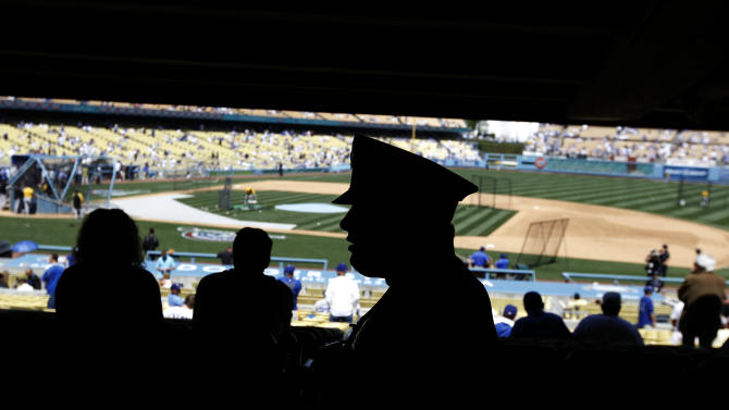 A members of the Los Angeles Police Department patrols the crowd before a baseball game between the Los Angeles Dodgers and the Pittsburgh Pirates in Los Angeles, Tuesday, April 10, 2012. Last year's opening day was marred by an attack at the end of the game on Giants fan Bryan Stow. He was wearing a team jersey when he was punched in the head, kicked and slammed to the ground in the parking lot. Stow, a paramedic from Santa Cruz, suffered severe brain damage and still has not recovered.(AP Photo/Chris Carlson)