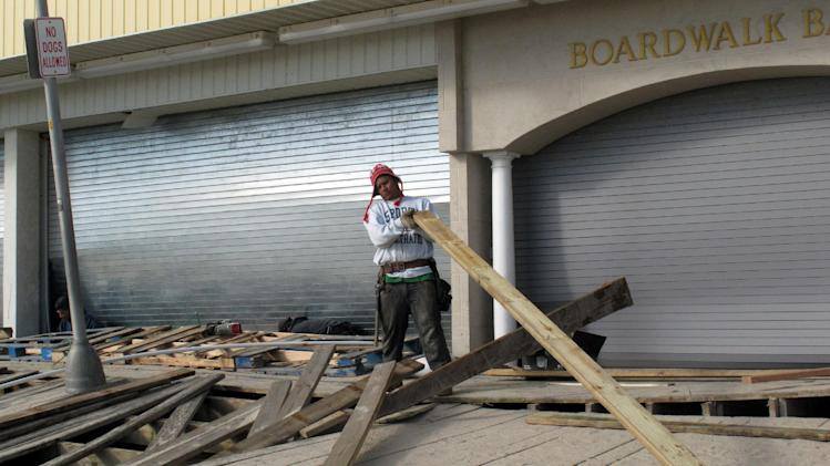 In this Nov. 1, 2012 photo, a worker removes damaged boards from the Point Pleasant Beach, N.J., boardwalk, three days after Superstorm Sandy wrecked parts of it. Coastal communities are racing to rebuild their boardwalks in time for next summer. (AP Photo/Wayne Parry)