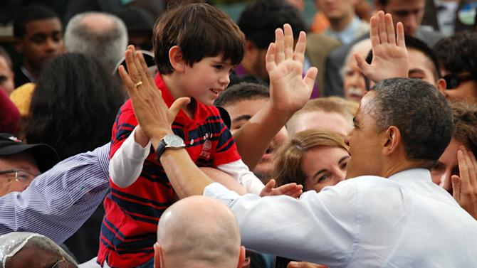 In this photo provided by Kathy Hackshaw, President Barack Obama greets a child during a campaign rally in Fairfax, Va., Friday, Oct. 19, 2012. (AP Photo/Courtesy Kathy Hackshaw) MANDATORY CREDIT