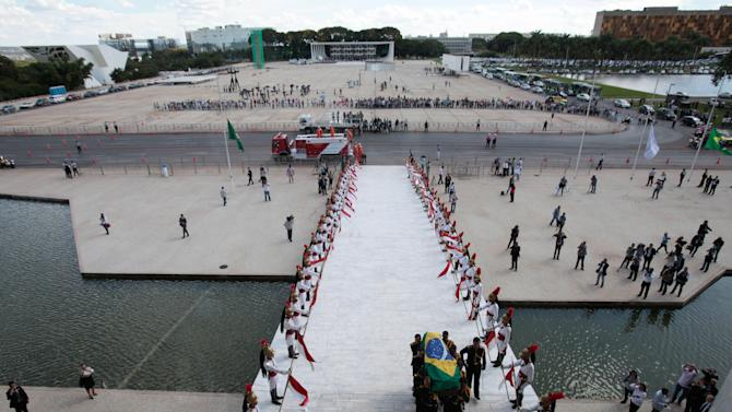 The flag-draped coffin containing the remains of Brazilian architect Oscar Niemeyer is carried past an honor and towards the entrance of the Planalto presidential palace, in Brasilia, Brazil, Thursday, Dec. 6, 2012. Niemeyer, 104, the groundbreaking architect who designed Brazil's futuristic capital and much of the United Nations complex, died Wednesday night in Rio de Janeiro, the seaside city where he was born and where his remains will be buried after he is honored with a service in Brasilia at the presidential palace he designed. (AP Photo/Eraldo Peres)