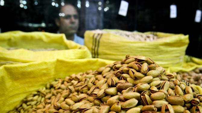 In this Sunday, March 31, 2013 photo, an Iranian man looks at pistachios for sale at a nut shop, in western Tehran, Iran. Pistachios are Iran's top non-oil export and provide work for hundreds of thousands of people. Still, Iranian authorities are backing a boycott. They laud it as a way to decrease domestic pistachio consumption and leave more nuts for exporting, which has become an increasingly important pipeline for foreign revenue as sanctions squeeze Iran's oil and gas sales. (AP Photo/Ebrahim Noroozi)