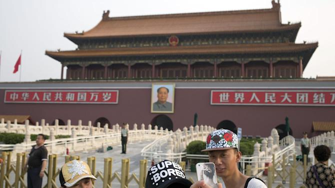 A Chinese woman takes a selfie on her mobile phone in front of Tiananmen Gate in Beijing Wednesday, June 4, 2014. Authorities in Beijing blanketed the city center with heavy security Wednesday on the 25th anniversary of the bloody military suppression of pro-democracy protests centered on Tiananmen Square. (AP Photo/Ng Han Guan)