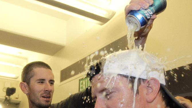 Oakland Athletics' pitcher Brandon McCarthy, left, douses a teammate with a beer as they celebrate in the clubhouse after their 12-5 win over the Texas Rangers in a baseball game, Wednesday, Oct. 3, 2012 in Oakland, Calif. The A's clinched the AL West title with the win. (AP Photo/Ben Margot)