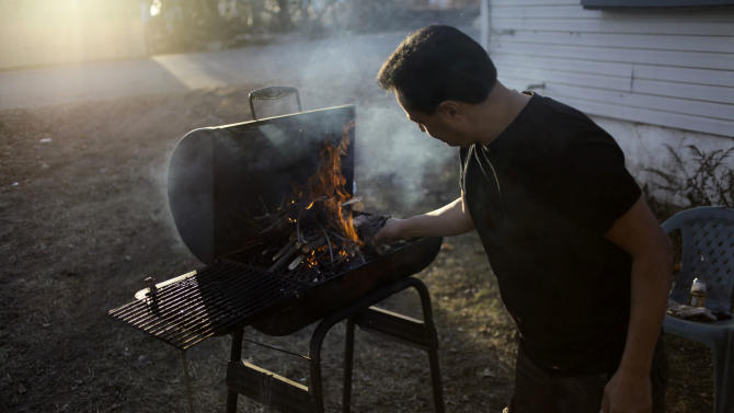 In this Monday, Dec. 3, 2012 photo, Amin Alhadad lights a fire in the grill to cook dinner for his family at his home in the Midland Beach section of Staten Island, New York. Amin, who emigrated to the U.S. years ago from Dubai, lost his job as a truck driver because he missed so much work after the storm. Their home was severely damaged during Superstorm Sandy, and they have been cooking many of their meals outside on the grill. (AP Photo/Seth Wenig)