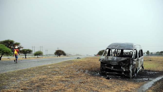 A man passes a burnt-out minibus taxi near the Amplats mine, Rustenburg, South Africa, Thursday, Oct. 11, 2012. Striking miners killed one man by setting him on fire Thursday while another was fatally shot, apparently by police, in rekindled labor unrest in South Africa that saw police firing tear gas and rubber bullets. (AP Photo/Str) SOUTH AFRICA OUT