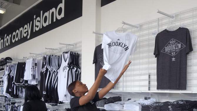 FILE - In this Thursday, May 23, 2013, file photo, a sales clerk Tanisha Thompson arranges T-shirts inside the new Nets Shop by Adidas in the Coney Island neighborhood of Brooklyn in New York. The government reports how much U.S. businesses adjusted their stockpiles in May on Monday, July 15, 2013. (AP Photo/Mark Lennihan)