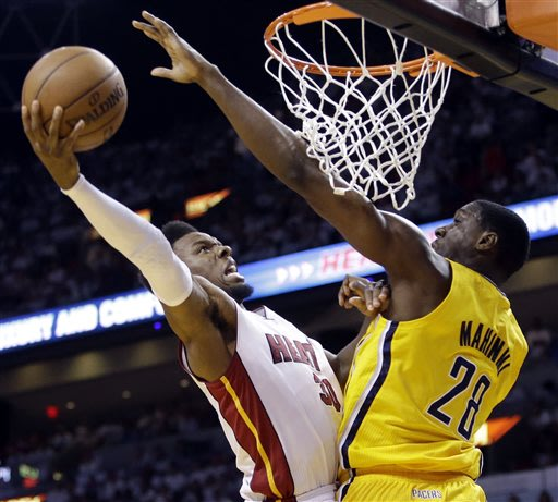 Miami Heat guard Norris Cole (30) attempts to score around Indiana Pacers center Ian Mahinmi (28) during the second half of Game 2 in their NBA basketball Eastern Conference finals playoff series, Fri