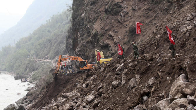 Chinese paramilitary policemen stand watch while rescuers operate backhoes to clear a damaged road due to a landslide triggered by a strong quake in Baosheng township of Lushan county in southwest China's Sichuan province Sunday April 21, 2013. Saturday's earthquake in Sichuan province killed over 200 people, China's Xinhua News Agency said. (AP Photo) CHINA OUT