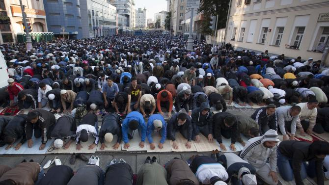 Muslim men, bowing toward Mecca, perform Eid al-Fitr prayers that mark the end of the holy fasting month of Ramadan outside a mosque in Moscow, Russia, on Sunday, Aug. 19, 2012. More than two hundred thousand Muslims gathered at Moscow's mosques to celebrate the Eid al-Fitr. (AP Photo/Alexander Zemlianichenko Jr)